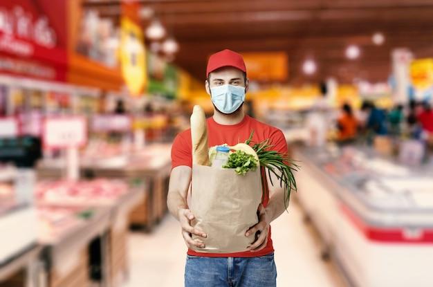 Работник доставочной компании держит продуктовый ящик, заказ еды, услуги супермаркета Premium Фотографии