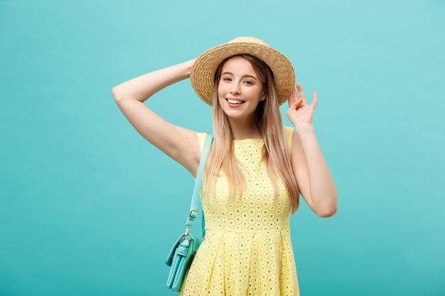 Концепция покупки и продажи: красивая несчастная молодая женщина в желтом элегантном платье с хозяйственной сумкой. Premium Фотографии