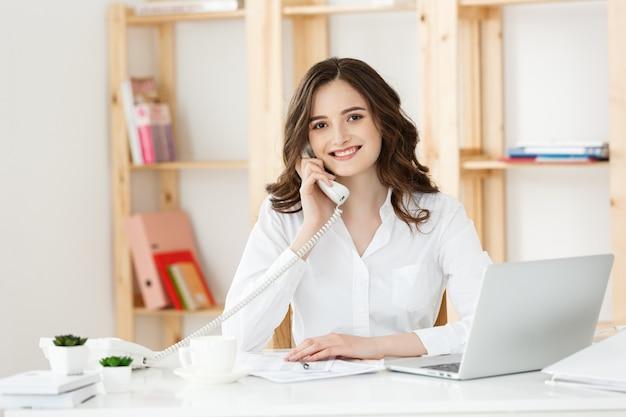 近代的なオフィスに電話で話している若い女性。 Premium写真