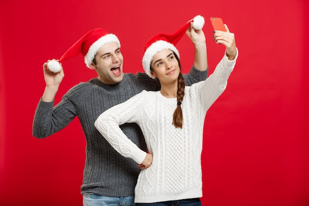 Молодой привлекательной пара, принимая самообороны на мобильный телефон, празднование в рождество. Premium Фотографии