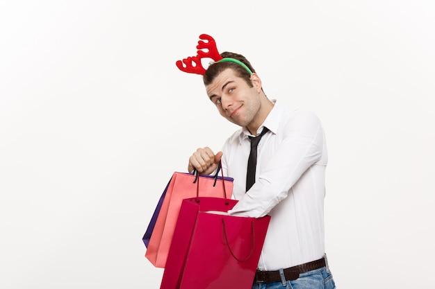 ハンサムなビジネスマンは、メリークリスマスと幸せな新年がトナカイヘアバンドを着て、サンタレッドの大きな袋を祝う。 Premium写真