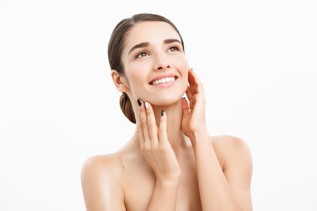 白い背景の上に完全なクリアな肌を持つ魅力的な若い女性。 Premium写真