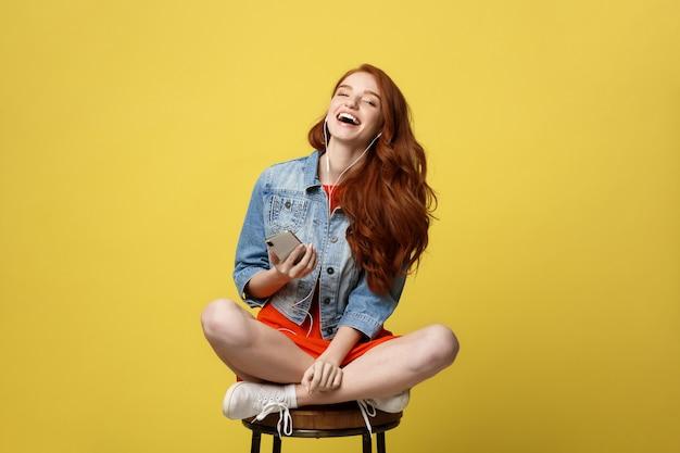 音楽を聞いて歌うイヤホンの幸せな女性 Premium写真