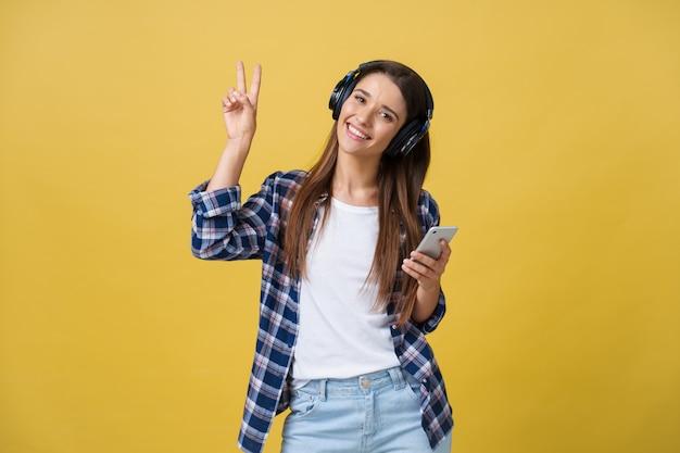 携帯電話で音楽を聴いて楽しい美しい白人女性の肖像画。 Premium写真