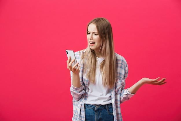 退屈の女の子、電話をかけてピンクの背景に夢中 Premium写真