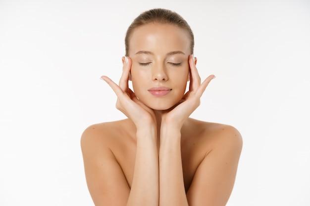 Красивая девушка улыбается с чистой кожей, естественный макияж и белые зубы на сером фоне. Premium Фотографии