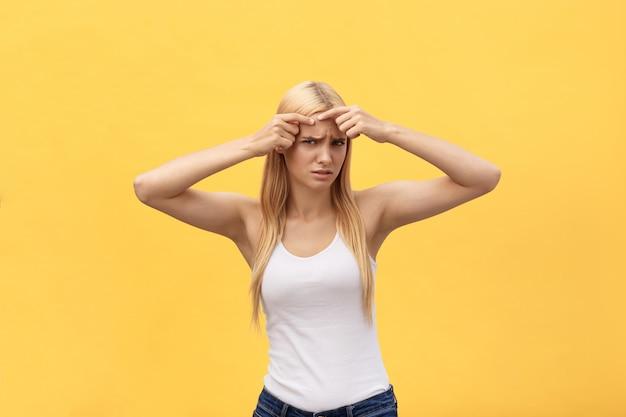 にきびの問題、顔、スパ、療法、治療、黄色の背景に分離されたに触れると心配している女の子のクローズアップの肖像画 Premium写真