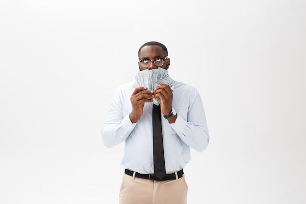 アフリカ系アメリカ人の実業家持株現金と深刻なカメラ目線。屋内、灰色の背景に分離されました。 Premium写真