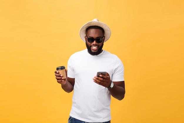 携帯電話でハンサムなアフリカ系アメリカ人とコーヒーカップを奪う。 Premium写真