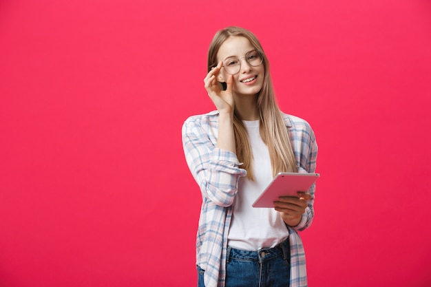 ピンクの背景に分離してカメラを見てタブレットコンピューターを使用して笑っている女性の肖像画 Premium写真
