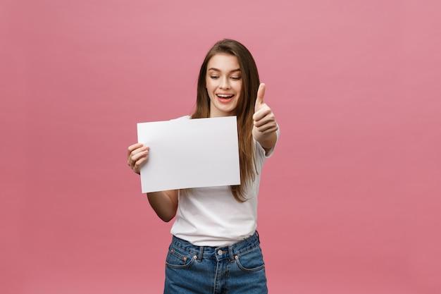 若い美しさの女性は空白のカードを保持し、ピンクの背景の上に親指を表示 Premium写真