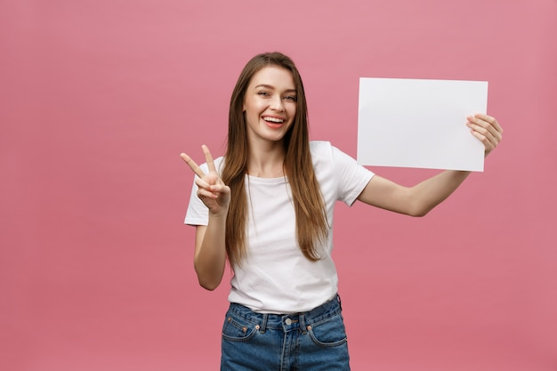 笑みを浮かべて、白い大きなモックアップを保持している肯定的な笑い女の肖像画を間近します。 Premium写真