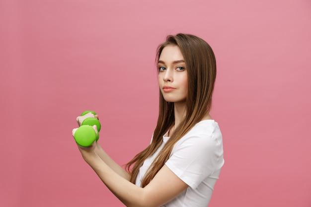 フィットネス、スタジオの背景でダンベルを持つ若い女。かわいい女の子をピンクの上分離 Premium写真