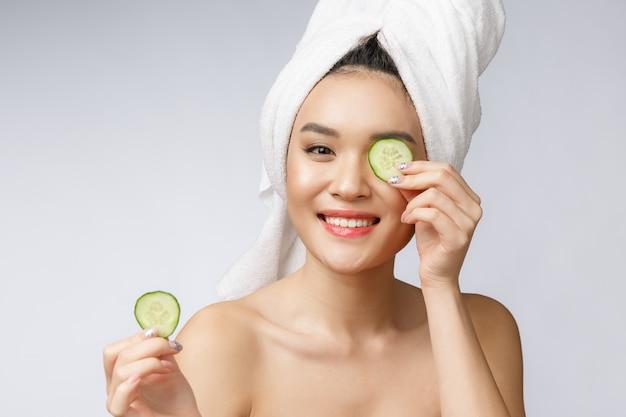 白い背景のスタジオでキュウリの美しさ若いアジア女性スキンケア画像。 Premium写真