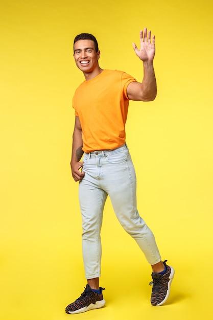 フレンドリーな若いハンサムな男の笑みを浮かべて、手を振って上げた Premium写真