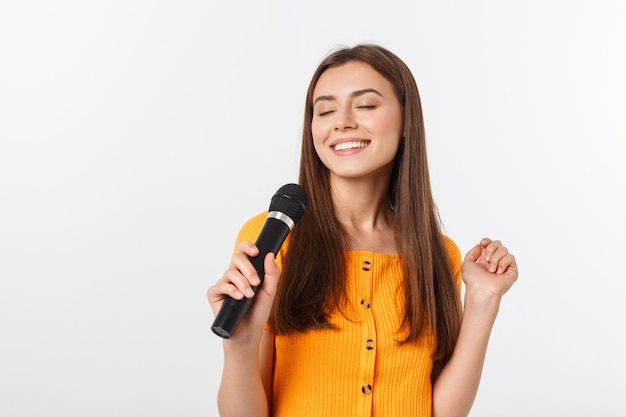 若いきれいな女性の幸せとやる気、マイクで歌を歌ったり、イベントを提示したり、パーティーをしたり、瞬間を楽しむ Premium写真
