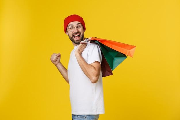 黄色に分離された幸せな気持ちで買い物袋を持つひげを生やした男 Premium写真