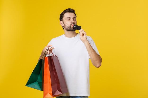 笑みを浮かべてカップル持株ショッピングバッグと黄色に分離されたクレジットカードの肖像画。 Premium写真