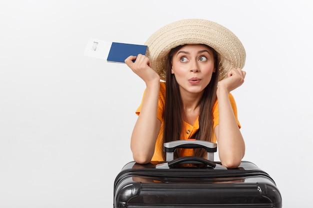 Концепция путешествия. портрет студии милой молодой женщины держа пасспорт и багаж. изолированные на белом Premium Фотографии