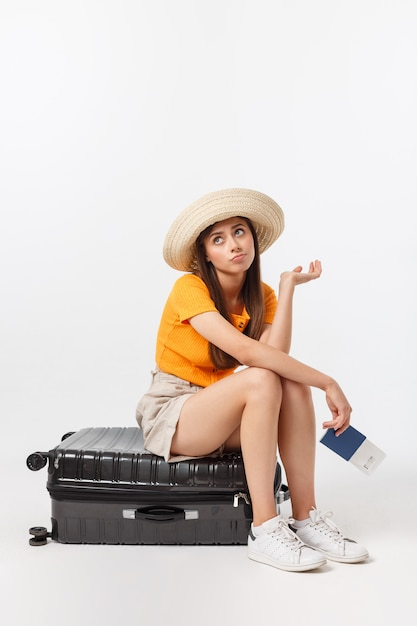 ライフスタイルと旅行の概念:若い美しい白人女性は、スーツケースの上に座って、彼女の飛行を待っています。白で隔離 Premium写真