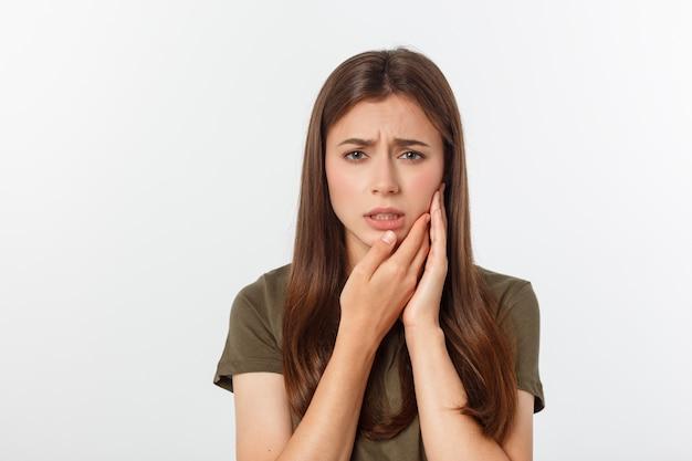 Подростковая женщина с болезненным выражением нажимает на ушибленную щеку, как будто у нее ужасная зубная боль Premium Фотографии