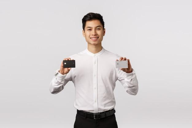 Нет денег в этом банке. довольный и нахальный красивый азиатский молодой предприниматель мужского пола, держа в руках две кредитные карты - черно-белую платину, улыбаясь доволен, рекомендует способ оплаты Premium Фотографии