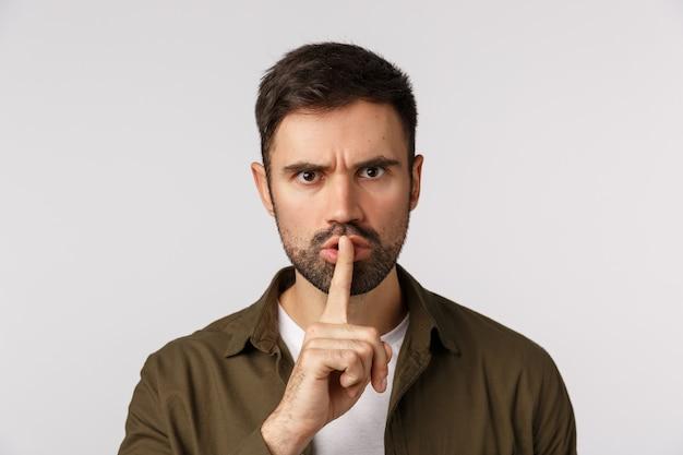 これについては黙っておく方が良いでしょう。攻撃的な、怒っている、不機嫌な白人のひげを生やした男性のコート、叫び声の需要は沈黙し、人差し指の唇で口を閉ざし、顔をしかめ、悩まされ、白い背景 Premium写真