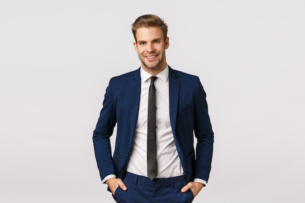 Красивый уверенный блондин бородатый бизнесмен, держась за руки в карманах, радостно улыбаясь, дать профессиональную атмосферу, обсуждая бизнес, удвоить свой доход, стать успешным, белый фон Premium Фотографии