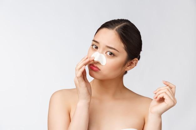 Косметология. портрет красивой женской азиатской модели с маской на носу. крупный план здоровой молодой женщины с чисто мягкой кожей и свежим естественным составом. Premium Фотографии
