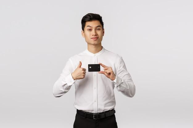 ハンサムな断定的なアジアの青年実業家は、クレジットカードを保持している銀行をお勧めします Premium写真