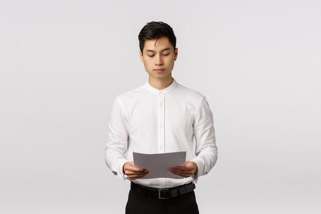 ビジネス、企業経済、人々の概念。真面目そうな忙しいエレガントなアジアの男性起業家が文書を保持、紙を読んで、オフィスの会議の準備、財務報告書の勉強 Premium写真