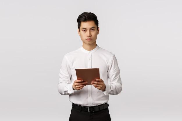 ビジネス、金融、採用コンセプト。ハンサムなエレガントな若いアジア人デジタルタブレットを保持していると深刻な探している忙しい、リモートコントロール作業、時間面接志願者 Premium写真
