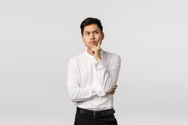 人生の意味を理解しようとしているハンサムなアジア系のビジネスマン、あごに触れる、真剣な集中式で見上げる、ビジネスコンセプトを考える、インスピレーションを検索、選択肢を熟考 Premium写真