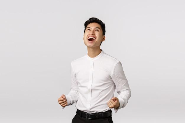 ええ、私が勝った神に感謝します。成功した取引を祝う男。喜んで、魅力的な若いアジア人の拳ポンプを喜ばせ、空でイエスと言い、ほっと笑顔で、目標を達成し、勝ちます Premium写真