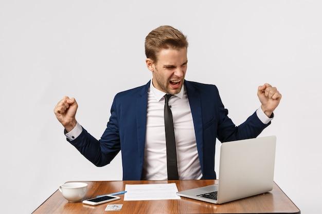 おいしく、成功とお祝いのコンセプト。陽気なイケメンボス、グッドニュースを祝う、チャンピオンダンスをして手を振って喜んで、勝利し、ラップトップを笑顔で見て、入札に勝つ Premium写真