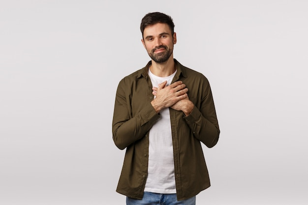 優しさ、幸福、愛の概念。優しい贈り物に感動し、感謝していると感じている優しいハンサムな男 Premium写真
