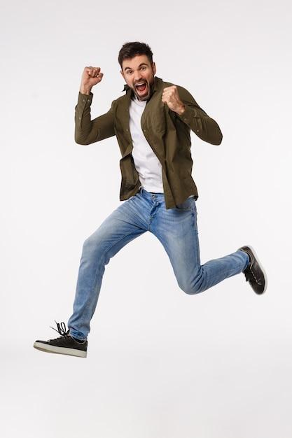 Достижения, поздравления и бизнес-концепция. привлекательный веселый человек прыгает от триумфа и праздника, достигает цели, выигрывает приз, сжимает руки доволен Premium Фотографии