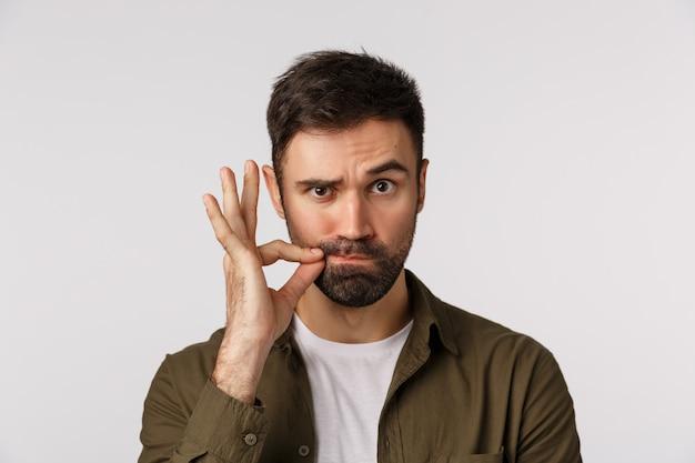 私の唇は約束で封印されています。深刻で面白いひげを生やした成人男性は口を閉じたままにし、ジップジェスチャーを行い、ヒントを与える人が沈黙を保つように片方の眉を上げる Premium写真