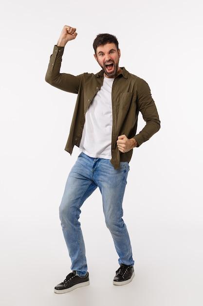 達成、成功、賞のコンセプト。カジュアルな服装のひげを持つ男性を喜ばせて喜ばせ、良いニュース、拳ポンプとダンスを祝い、明るい笑顔 Premium写真