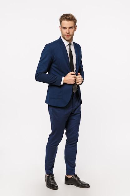 優雅さ、自信、ビジネスコンセプト。ハンサムな若いひげを生やした金髪のビジネスマンのスーツとネクタイ、ジャケットを修正し、真剣で自信を持って、決心をする Premium写真