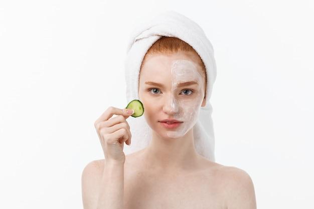 美しいきれいな肌を持つ魅力的な若い女性。白いマスクとキュウリ。美容トリートメントと美容スパセラピー。 Premium写真