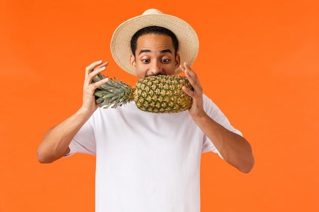 Забавный красивый хипстерский парень, афроамериканский турист, наслаждающийся отпуском, пробующий укус ананаса, смотрящий на фрукты, радостно стоящий на оранжевой стене, словно путешествует по жарким странам зимой Premium Фотографии