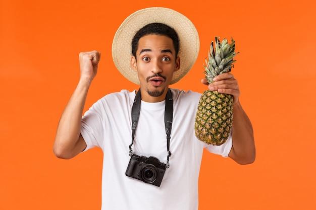 Ура отпуск и тропические фрукты. веселый возбужденный афроамериканец наконец-то уехал за границу, развлекался во время поездки, кулаком и держал ананас, стоя над оранжевой стеной Premium Фотографии