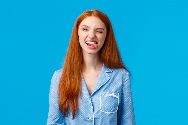 Беззаботная и забавная милая рыжая девочка-подросток не хочет спать во время ночевки с подружками, показывает язык и дурачится, высмеивает гримасы, радостно подмигивает, носит пижаму, голубые стены Premium Фотографии