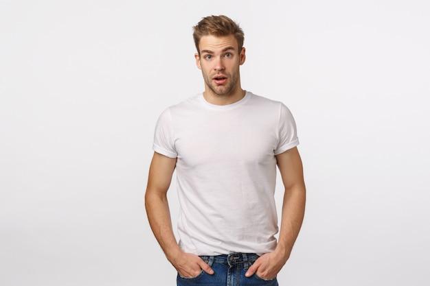 Привлекательный белокурый бородатый мужчина в белой футболке позирует Premium Фотографии