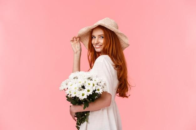 ピンクのボーイフレンドといちゃつくロマンチックな、愚かな、柔らかいかわいい赤毛の女性、かわいい帽子、ドレス、花束の白い花を持って、カメラを回して、コケティッシュな笑みを浮かべて Premium写真