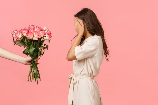 Великолепная женственная кавказская женщина в маскарадном костюме, закрывающая глаза ладонями в ожидании сюрприза, рука, держащая прекрасный букет роз, тайный поклонник, выражающий любовь с подарком, розовый Premium Фотографии