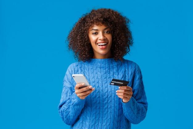 陽気な見栄えの良いアフリカ系アメリカ人女性のオンライン購入、割引ホリデーシーズン中のショッピング、笑みを浮かべて、スマートフォンとクレジットカードを保持、青い立ち Premium写真