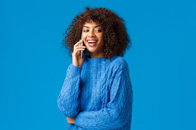 こんにちは。かわいいフレンドリーでカリスマ的なアフリカ系アメリカ人女性の友人の大日のパーティーを招待して、一緒に休日を祝う、電話で仲間を呼ぶ、スマートフォンを保持し、笑う Premium写真