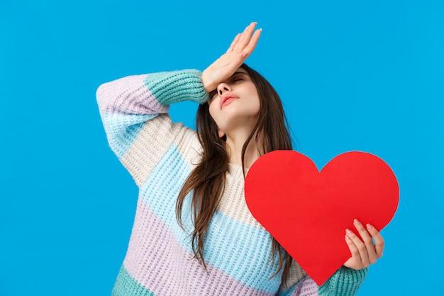 Брюнетка в зимнем свитере держит красное сердце Premium Фотографии